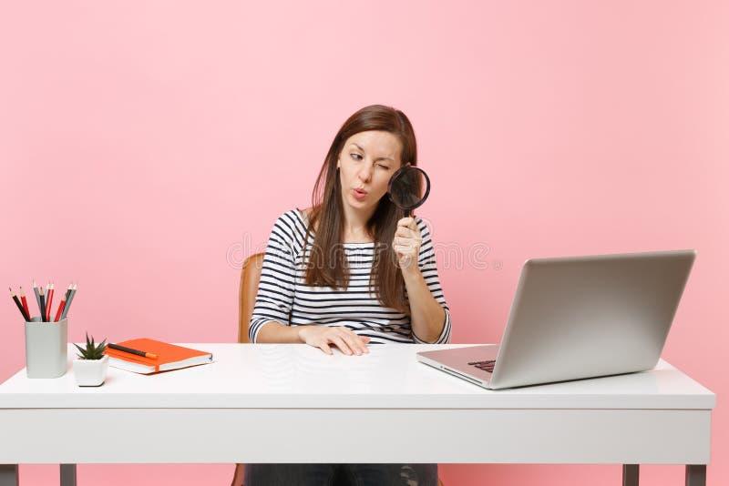Молодая любопытная женщина всматриваясь смотреть через лупу на ноутбуке ПК пока сидите работа на проекте на офисе стоковое изображение