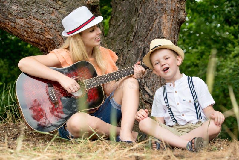 Молодая мать и красивые остатки сына в лесе, поют песни под гитарой стоковое изображение