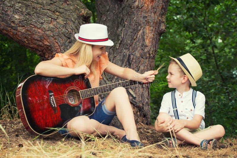 Молодая мать и красивые остатки сына в лесе, поют песни под гитарой стоковая фотография rf