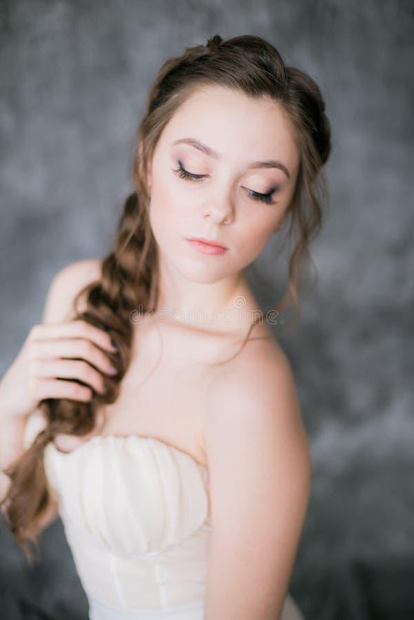 Молодая милая невеста с красивым hairdo в белом платье на серой предпосылке стоковые фото