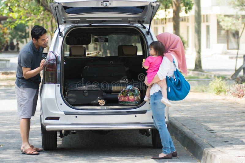 Молодая мусульманская семья, переход, отдых, концепция поездки и людей - счастливый человек, женщина и маленькая девочка играя с  стоковое изображение rf