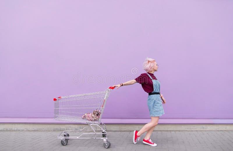 Молодая модель представляет с тележкой на предпосылке пурпурной стены стоковые фото