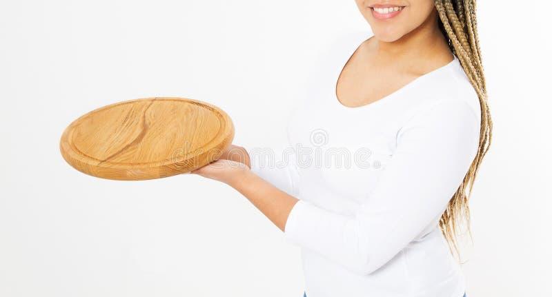Молодая привлекательная Афро-американская женщина держа пустую деревянную разделочную доску пиццы изолированный на белой предпосы стоковое фото rf