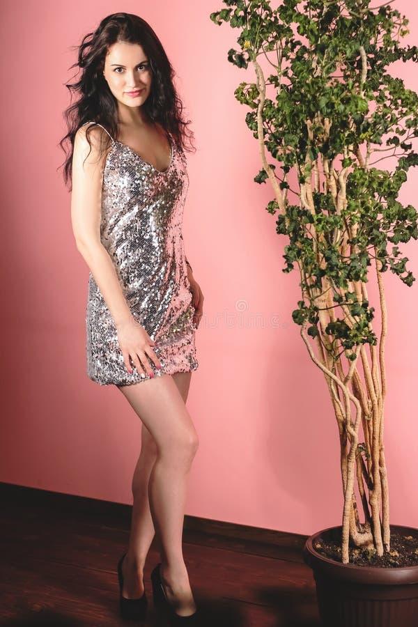 Молодая привлекательная девушка брюнета представляя в гениальном серебряном платье в студии фото на розовой предпосылке стоковое изображение