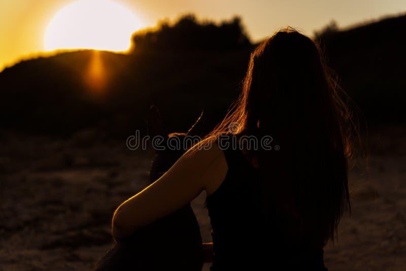 Молодая привлекательная девушка с ее xoloitzcuintli собаки восхищая заход солнца стоковое фото
