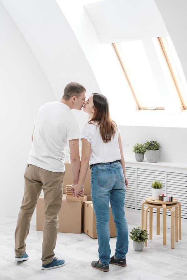 Молодая семья, человек и женщина в белых одеждах в светлой комнате на предпосылке картонных коробок и вещей стоковое изображение