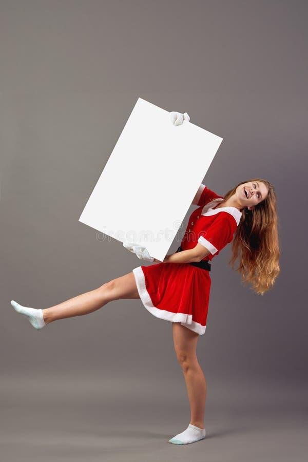 Молодая славная Госпожа Санта Клаус одел в красной робе, белых перчатках и белые носки поднимают вверх белый холст на сером цвете стоковая фотография rf