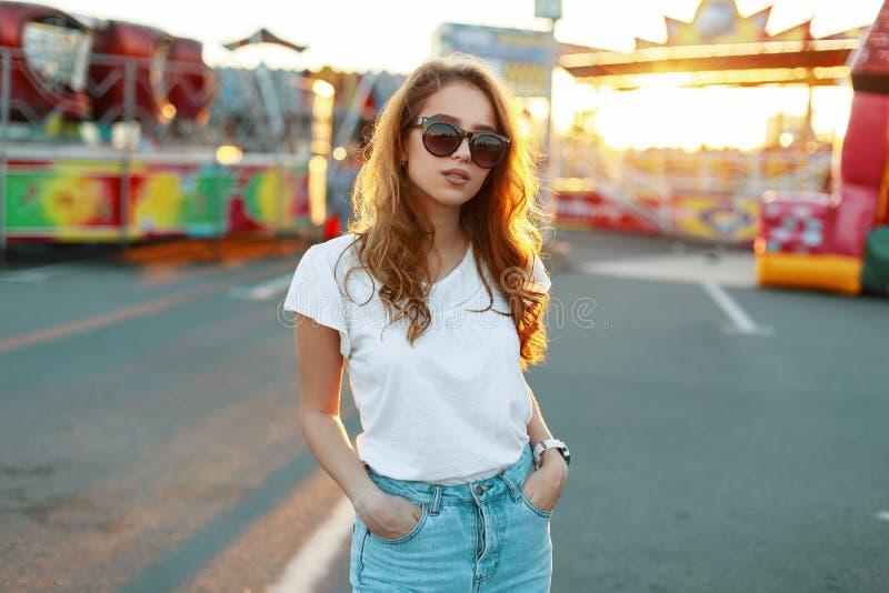 Молодая стильная женщина хипстера в ультрамодных джинсах в стильных солнечных очках в ультрамодной футболке наслаждается ярким св стоковое изображение rf