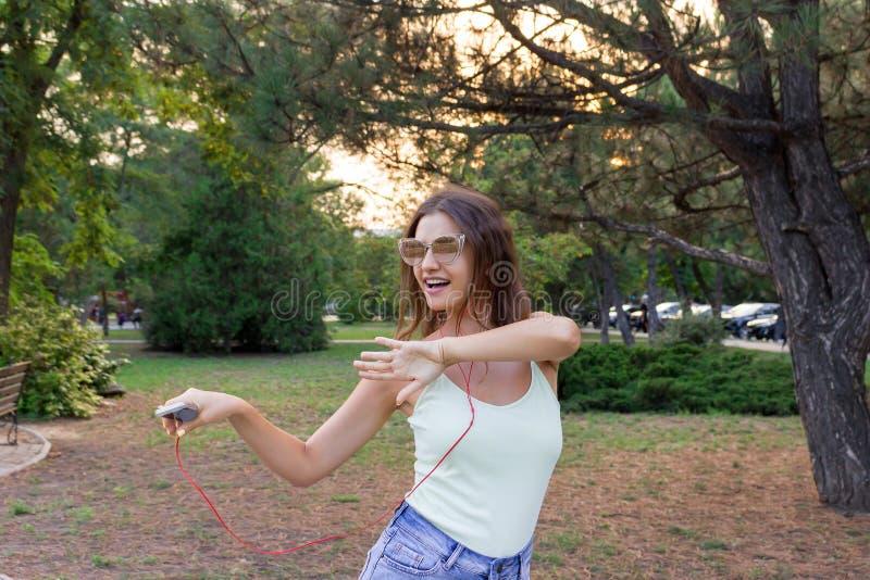 Молодая стильная милая девушка слушает музыку в наушниках на мобильном телефоне и танцует в парке Милая женщина ослабляет и стоковая фотография rf