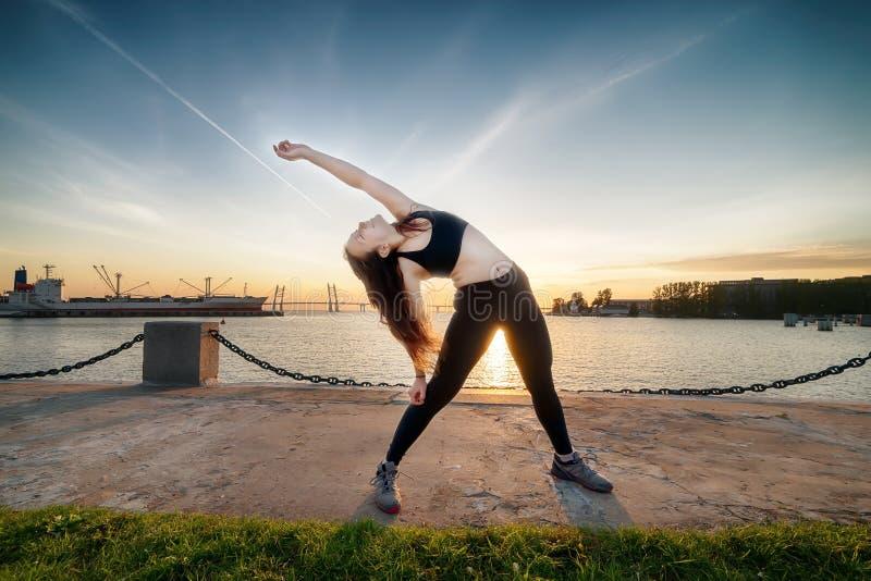 Молодая счастливая атлетическая смотря девушка делая гимнастику на заходе солнца стоковое фото rf