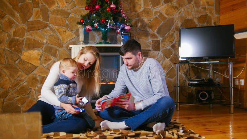 Молодая счастливая семья сидя на поле в уютном доме стоковые изображения