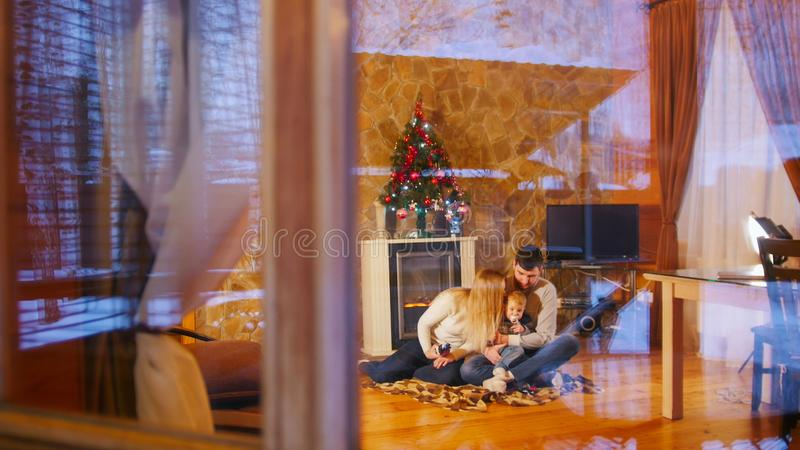 Молодая счастливая семья сидя на поле в уютном доме осмотрите окно стоковое изображение rf