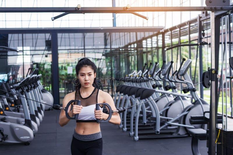 Молодая разминка тренировки женщины фитнеса с кабелем тренировк-машины в спортзале фитнес-центра уклад жизни принципиальной схемы стоковое фото