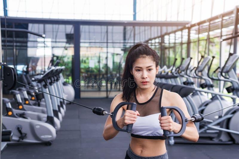Молодая разминка тренировки женщины фитнеса с кабелем тренировк-машины в спортзале фитнес-центра уклад жизни принципиальной схемы стоковая фотография