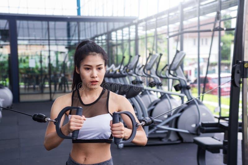 Молодая разминка тренировки женщины фитнеса с кабелем тренировк-машины в спортзале фитнес-центра уклад жизни принципиальной схемы стоковые изображения