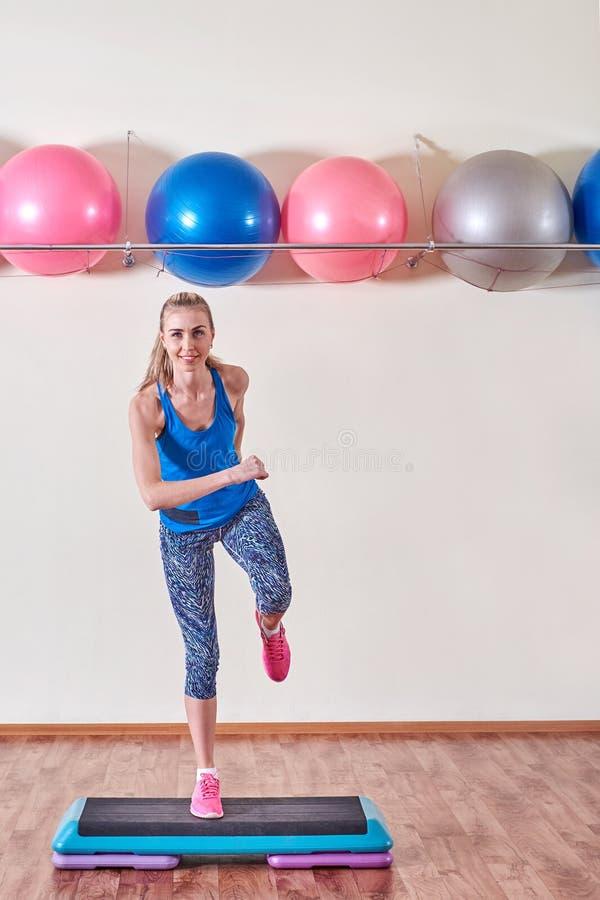 Молодая sportive женщина работая в спортзале используя платформу шага стоковые изображения rf