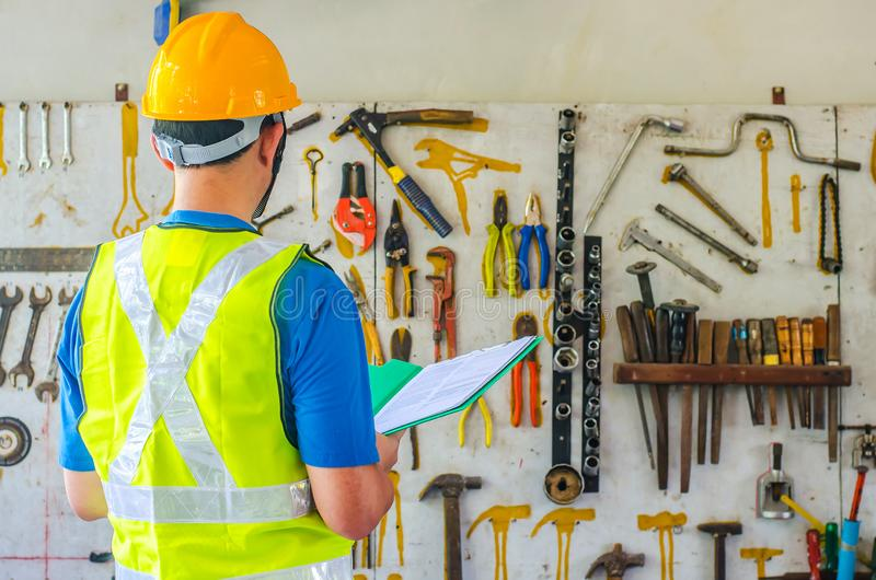 Молодые азиатские мужские файлы удерживания инженера или архитектора нося защитный шлем безопасности около много различных ржавых стоковая фотография rf