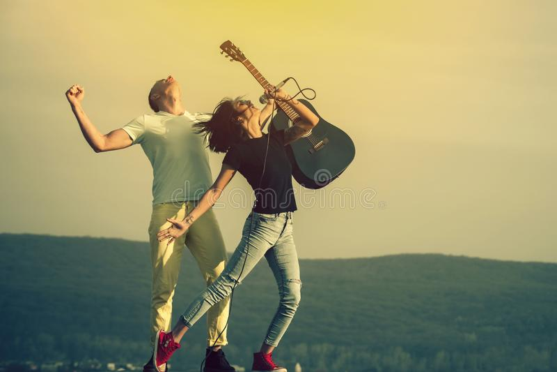 Молодые пары музыкантов выполняя на естественном этапе стоковая фотография rf