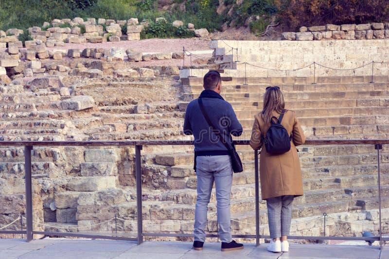 Молодые пары: парень и девушка с рюкзаком посещая римский театр Малага руина стоковая фотография rf