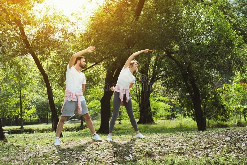 Молодые пары протягивая в парке стоковые фото