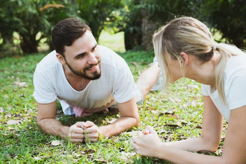 Молодые пары протягивая в парке стоковые изображения