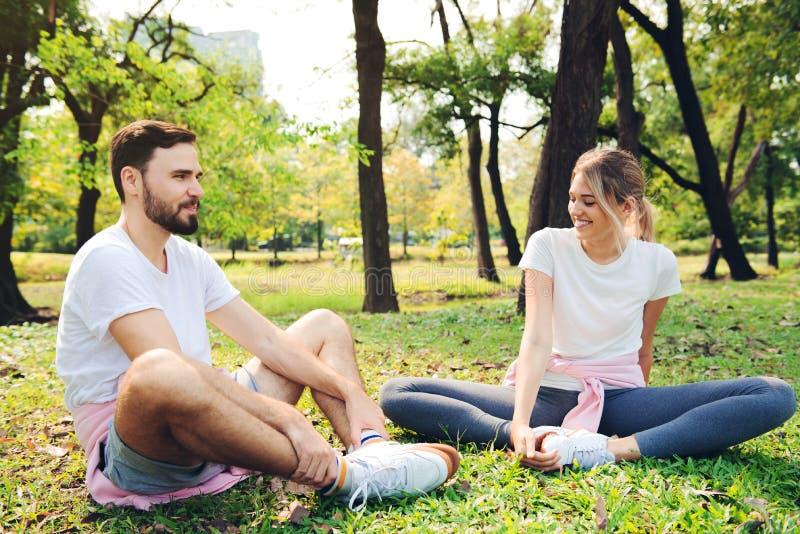 Молодые пары протягивая на парке стоковая фотография