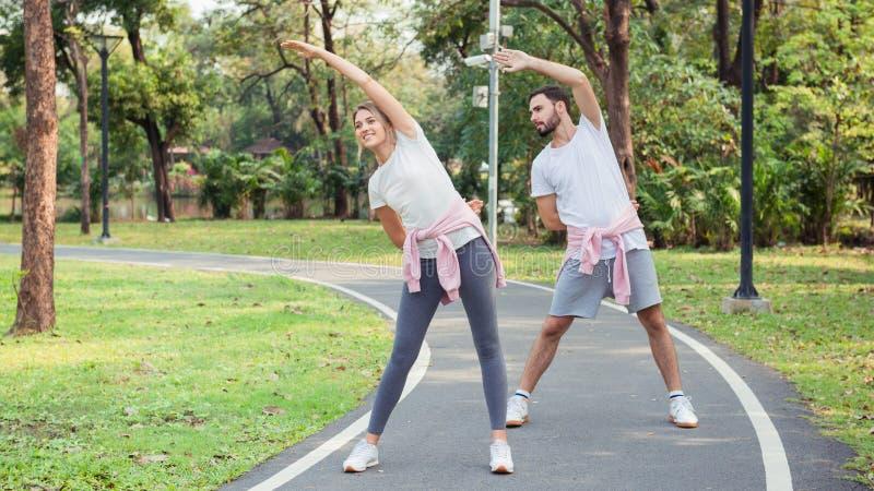 Молодые пары протягивая на парке стоковые изображения
