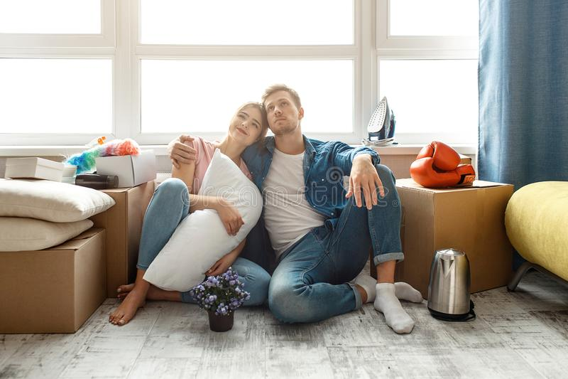 Молодые пары семьи купили или арендовали их первую небольшую квартиру 2 люд сидят на поле и смотрят вверх Они мечты ванта стоковая фотография