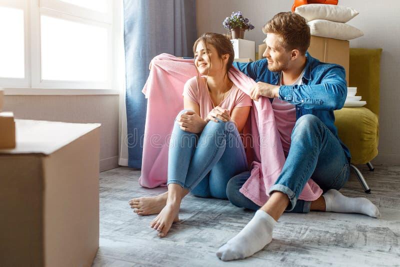 Молодые пары семьи купили или арендовали их первую небольшую квартиру Счастливые люди сидят совместно на поле и взгляде на окне стоковое изображение rf