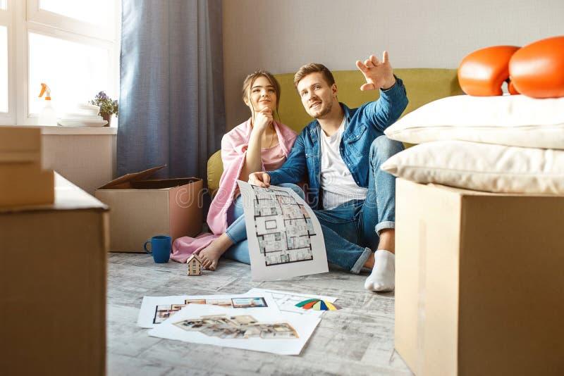 Молодые пары семьи купили или арендовали их первую небольшую квартиру Люди сидят совместно на поле Пункт Гай вперед Он стоковые фото