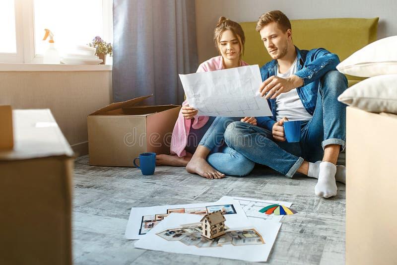 Молодые пары семьи купили или арендовали их первую небольшую квартиру Они сидят на поле и смотрят совместно на плане квартиры стоковое изображение rf