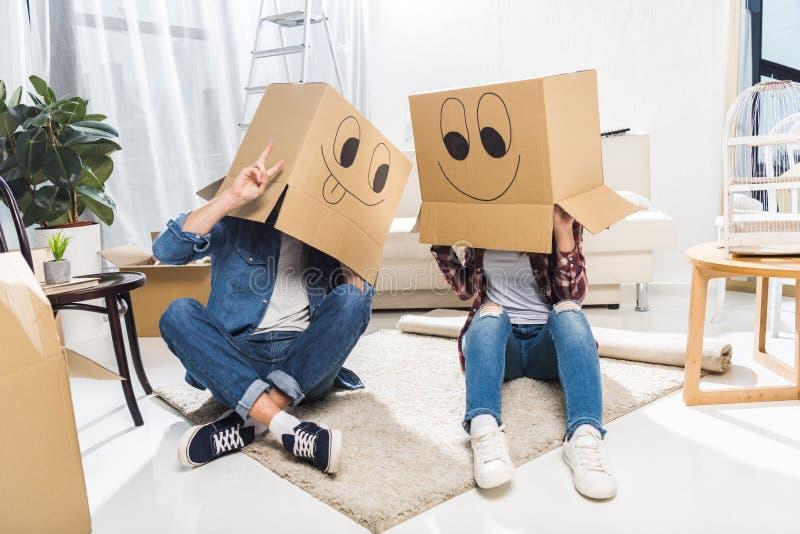 Молодые пары сидя на поле с коробками на их головах которые имеют smiley стороны стоковая фотография rf