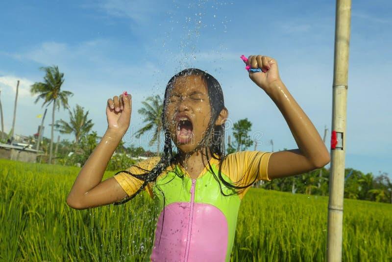 Молодые счастливые и беспечальные красивые леты outdoors ребенка 7 или 8 старого имея ливень на красивой террасе риса шаловливой  стоковые фото