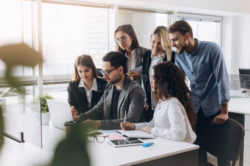 Молодые творческие менеджеры объединяются в команду работа с новым проектом в современном офисе стоковое изображение rf