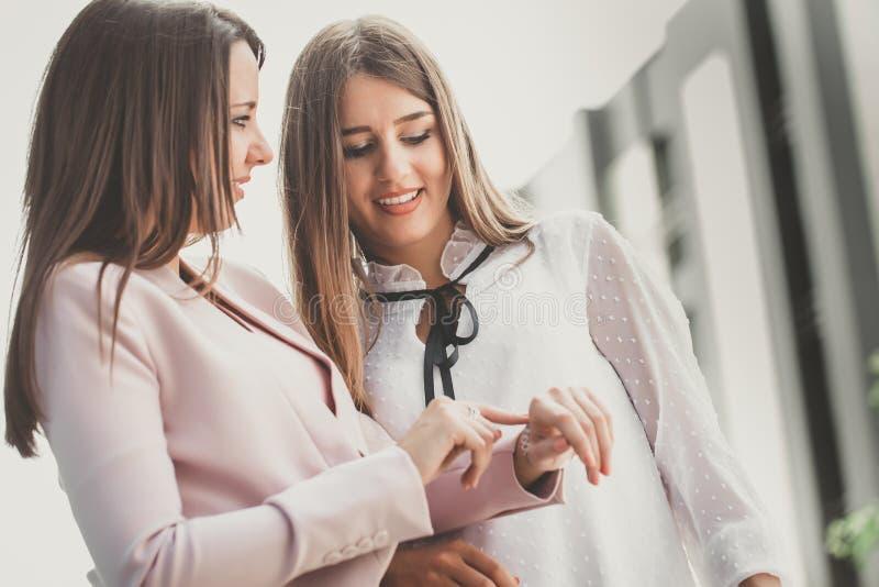 2 молодых бизнес-леди говоря и проверяя время на дозоре стоковое изображение