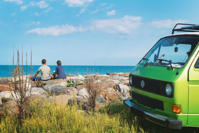 2 молодых путешественника сидя на кофе скалистого пляжа выпивая и смотря к морю Старый жилой фургон таймера припаркованный позади стоковые фотографии rf