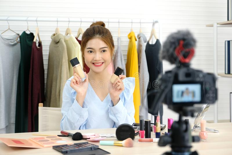 Молодой азиатский блоггер красоты женщины показывая как составить видео- консультационную запись камерой, концепцией vlog, людьми стоковое изображение rf