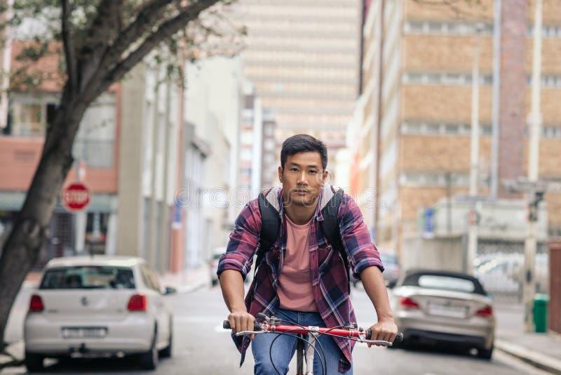 Молодой азиатский человек ехать его велосипед через город стоковые фото