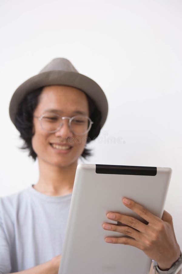 Молодой азиатский человек со шляпой и стеклами fedora используя планшет и усмехаться используя планшет на внутри помещения зоне в стоковая фотография