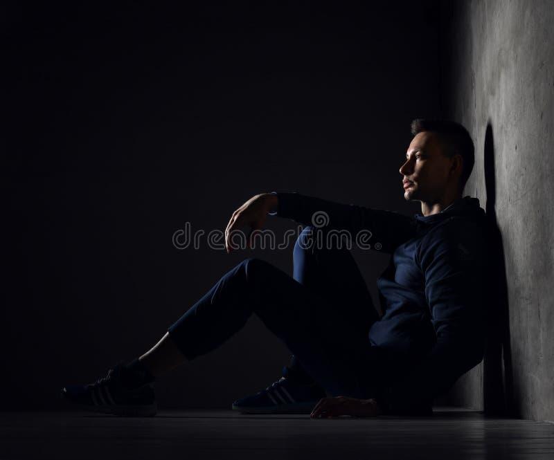 Молодой атлетический человек в голубом trainsuit носки спорта сидит на поле бетонной стеной и смотрит вперед стоковая фотография