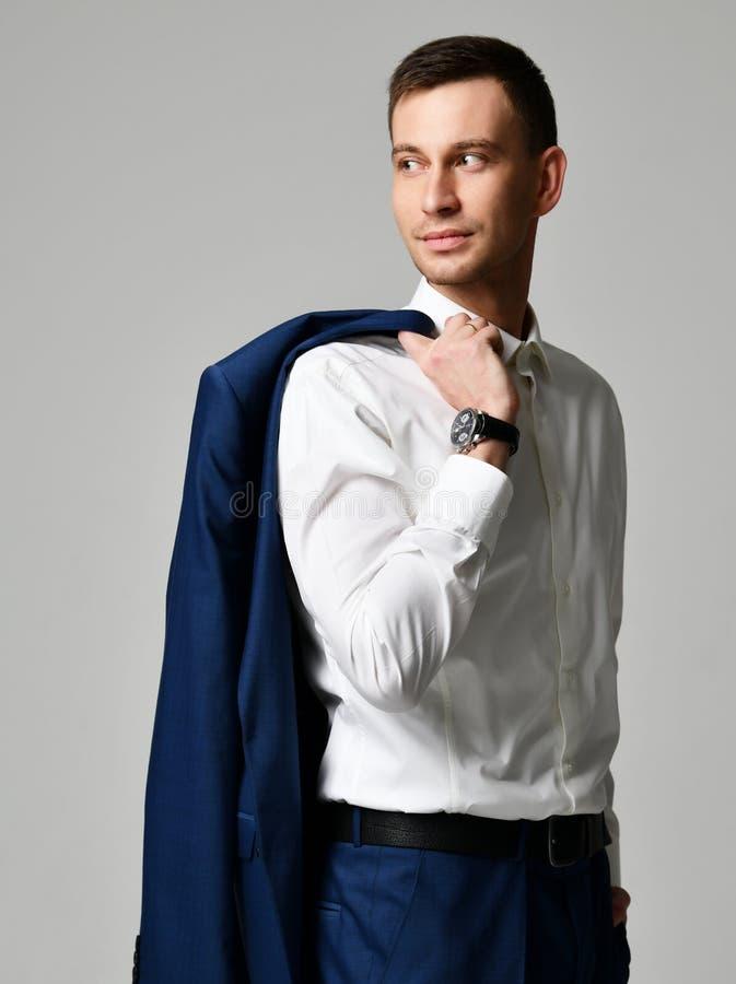 Молодой бизнесмен в голубом официальном костюме рассматривает его плечо стоковое фото