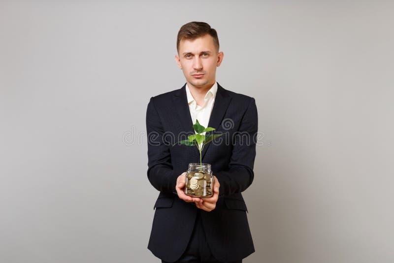 Молодой бизнесмен в классической черной рубашке костюма держа золотые монеты кучи в стеклянном опарнике с зеленым растением пуска стоковые фотографии rf