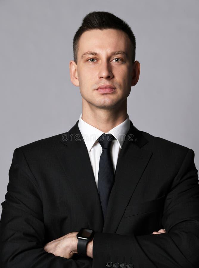 Молодой бизнесмен в классическом официальном костюме осторожно слушать что-то или смотреть что-нибудь во время встречи стоковые фото