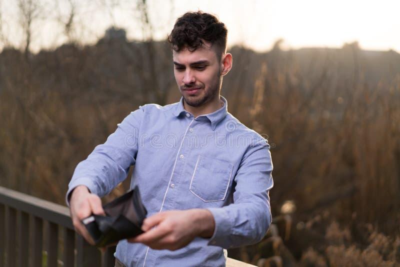 Молодой бизнесмен смотря его бумажник стоковое фото