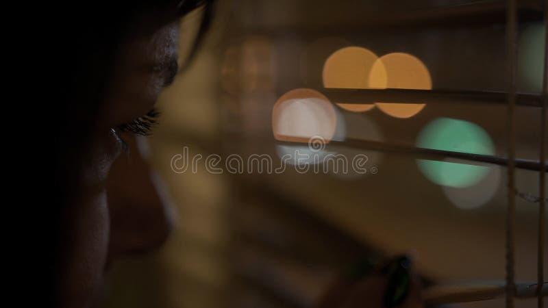 Молодой брюнет с коричневыми взглядами украдкой глаз через окно с ее пальцем, нажимая раскрывает шторки стоковые фото