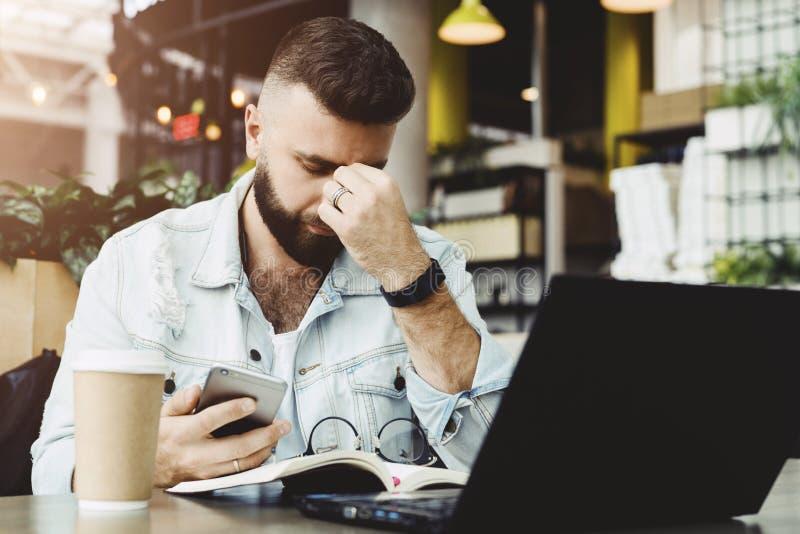 Молодой бородатый унылый бизнесмен сидит на таблице, покрывая его сторону с его рукой и держа smartphone в его руке стоковая фотография rf
