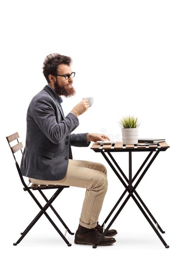 Молодой бородатый человек держа кофейную чашку и сидя на таблице стоковые изображения