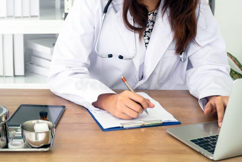Молодой женский врач используя ноутбук стоковое изображение rf