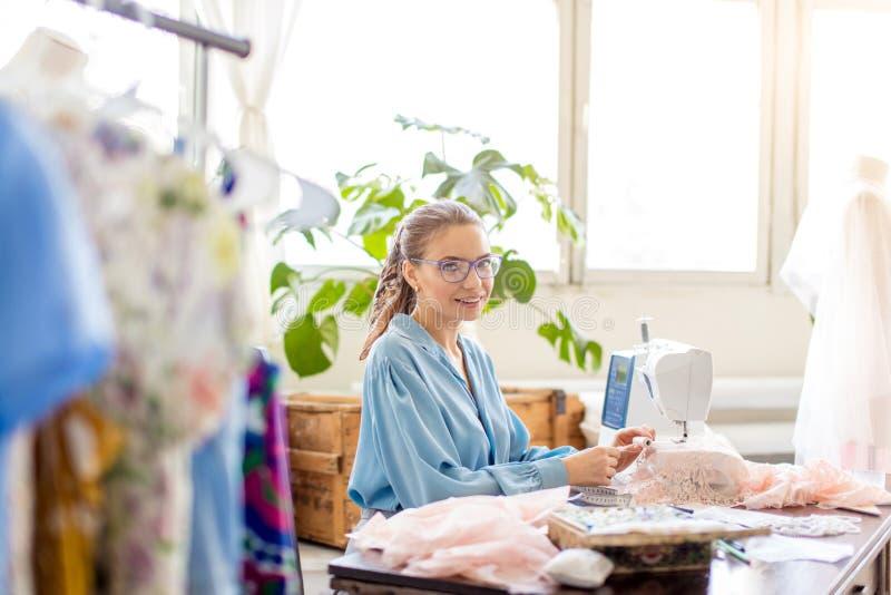 Молодой женский портной сидит на рабочем месте и выбирает цвет потоков в atelier стоковая фотография rf