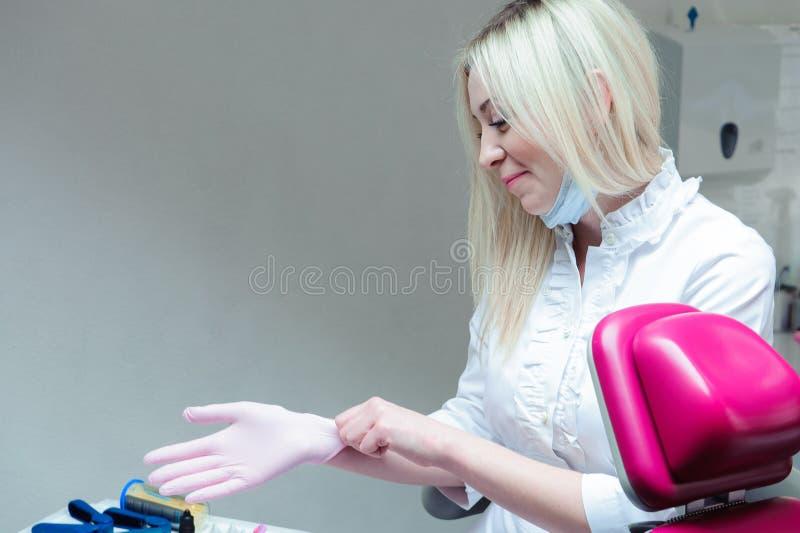 Молодой женский доктор подготавливая для работы, кладущ на защитные перчатки стоковое фото rf